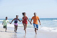 Family running in waves on beach