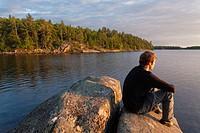 A man sitting on a rock as the sun sets over Georgian Bay. Massasauga Provincial Park, Ontario, Canada.