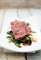 Tuna sashimi with sesame on a bed of seaweed