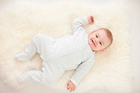 Smiling baby laying on rug
