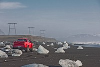 Off road vehicle parked on iceberg beach, Jokulsarlon, South East Iceland, Iceland