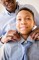 Father adjusting son's tie