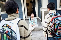 Hispanic mother greeting sons at door