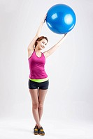 a woman holding up the yoga ball