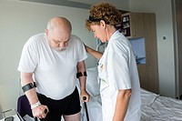 Tilburg, Netherlands. Physio therapist instructing a male post operative patient on how to walk again, after reviving a new hip in surgery.
