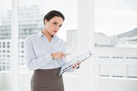 Elegant businesswoman with graphs in office