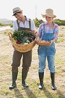 Full length of smiling couple with vegetables in field