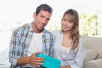 Loving couple with gift box sitting on sofa