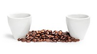 heap of coffee beans with two cups