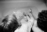 Women Washing Cat in Bathtub
