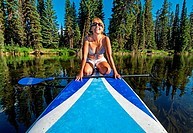 A woman riding the Stand Up Paddle Board on the North Fork of the Payette River near Payette Lake and the city of McCall in the Salmon River Mountains...