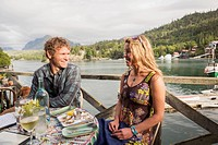 A couple in their 30's enjoys dinner at the Saltry Restaurant in Halibut Cove, Kachemak Bay, Southcentral Alaska.