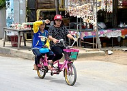 Two women riding a tandem, Cha Am, Thailand