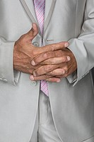 Midsection of businessman standing with hands clasped