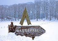 snowy landscape with direction sign to the waterfall Plaesterlegge, Germany, North Rhine-Westphalia, Bestwig