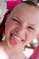 Portrait of a 10 year old girl with freckles sticking her tongue out at the camera making a funny face.