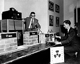 Atomic energy display. 1950 image showing two men setting up a display based on information relating to the study of atomic energy and radioactivity. ...