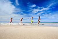 children running along sandy beach, Scotland.