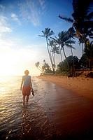 Young woman walking on Hikkaduwa beach at sunset, Sri Lanka.