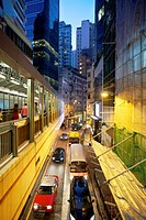 pedestrians use elevated walkway over traffic through Soho district at dusk, Hong Kong.