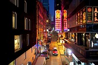 elevated view of taxi driving through neon lit restaurants and shops in Soho district, Hong Kong.