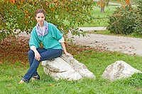 Woman in aqua sweater and blue jeans seated on a rock.