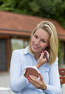 Pretty blonde woman making-up in a Cafe outdoors