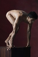 Nude man crouching in starting position, full length
