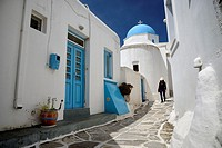 Woman walking in a narrow street in the village of Lefkes, small church with a blue dome. Greece, Greek islands in the Aegean sea, the Cyclades, Paros...