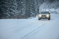 Truck driving on snowy road, winter driving, Norway