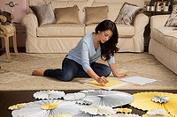 Hispanic woman making paper crafts in living room