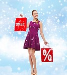 sale, gifts, christmas, holidays and people concept - smiling woman in purple dress holding shopping bags with percentage sign over blue sky and cloud...