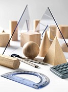 Geometric wooden shapes used in maths and calculus education with geometry set and calculator.