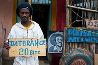Rasta young man holding a entrance 20 birr panel in front of the shop where he sells Rasta art. Shashemene ( Ethiopia).