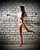 Young dancing woman on grey brick wall background (dark version)