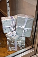 Wrapped Gift Packages Stacked in the Display Window of a New York City Retail Store, signifying Christmas Gifts that one should purchase in that store...