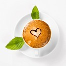 large cup of coffee with heart pattern on the foam and green leaf of mint