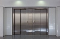 Two brushed metal elevator doors in a minimalistic style building interior