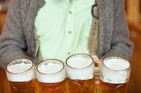 Waiter holding 4 Mass beer jugs at Oktoberfest, Munich, Germany