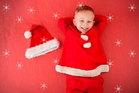 Composite image of little boy in santa costume