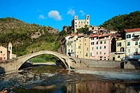 Stone bridge Ponte Vecchio across the Nervia river with residential buildings and the remains of the old fortress Castello dei Doria and church, Dolce...