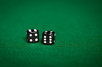 gambling, fortune, game and entertainment concept - close up of black dice on green casino table
