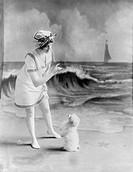 Bathing beauty, young woman in bathing suit with small dog in front of studio backdrop of beach, photograph, 1913.