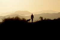 Woman and dog early morning in field, Thousand Oaks, California, USA