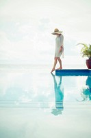 Caucasian woman dipping toe in swimming pool