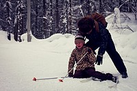 Caucasian father helping cross-country skiing daughter falling in snow