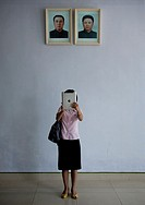 Woman With Ipad In Front Of Portraits Of Kim Il Sung And Kim Jong Il, Panmunjeon, North Korea