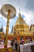 Asia. Thailand, Chiang Mai. Wat Doi Suthep. The faithful pray by going around the chedi.