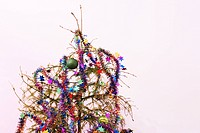 End of the holidays or other concept: dead fir Christmas tree with dried up needles star garland and ornaments left in the tree.
