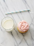 A rose cupcake with a glass of milk